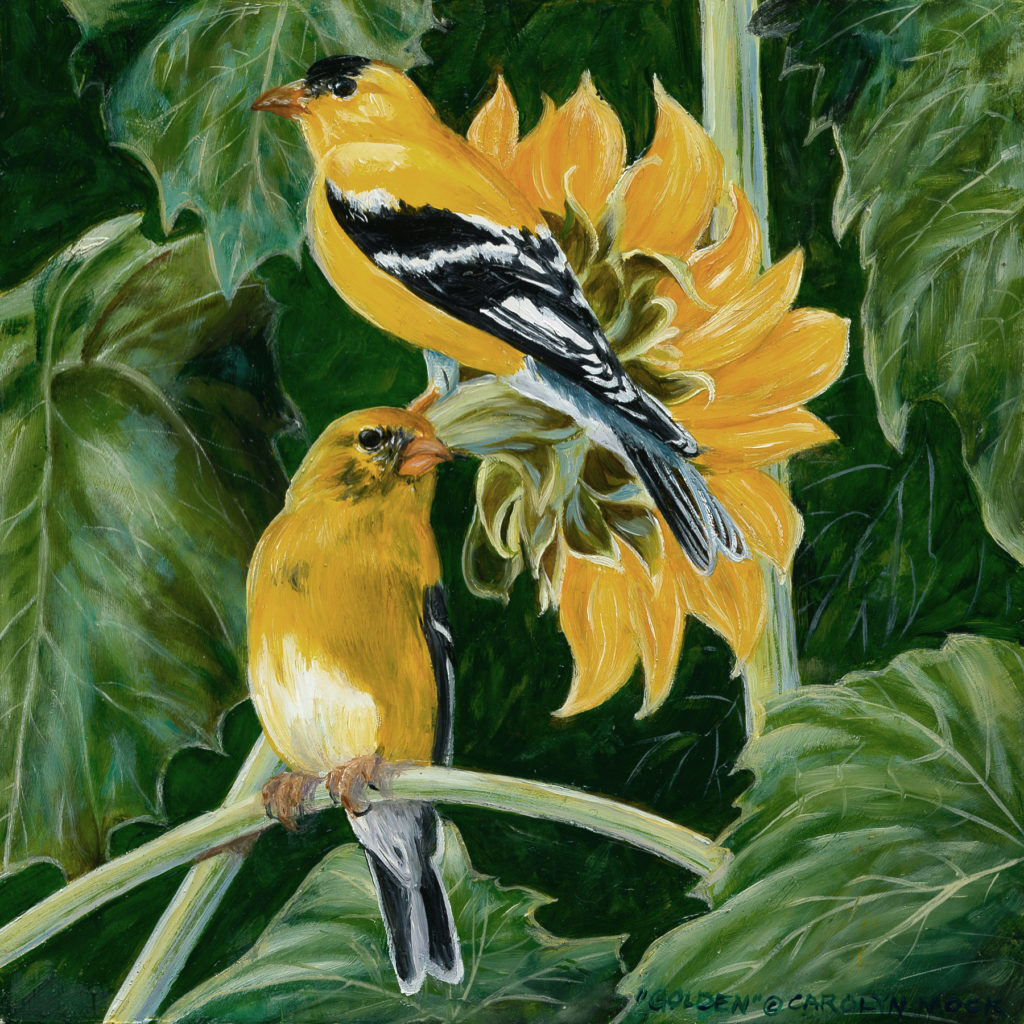 Two gold birds perched on leaves