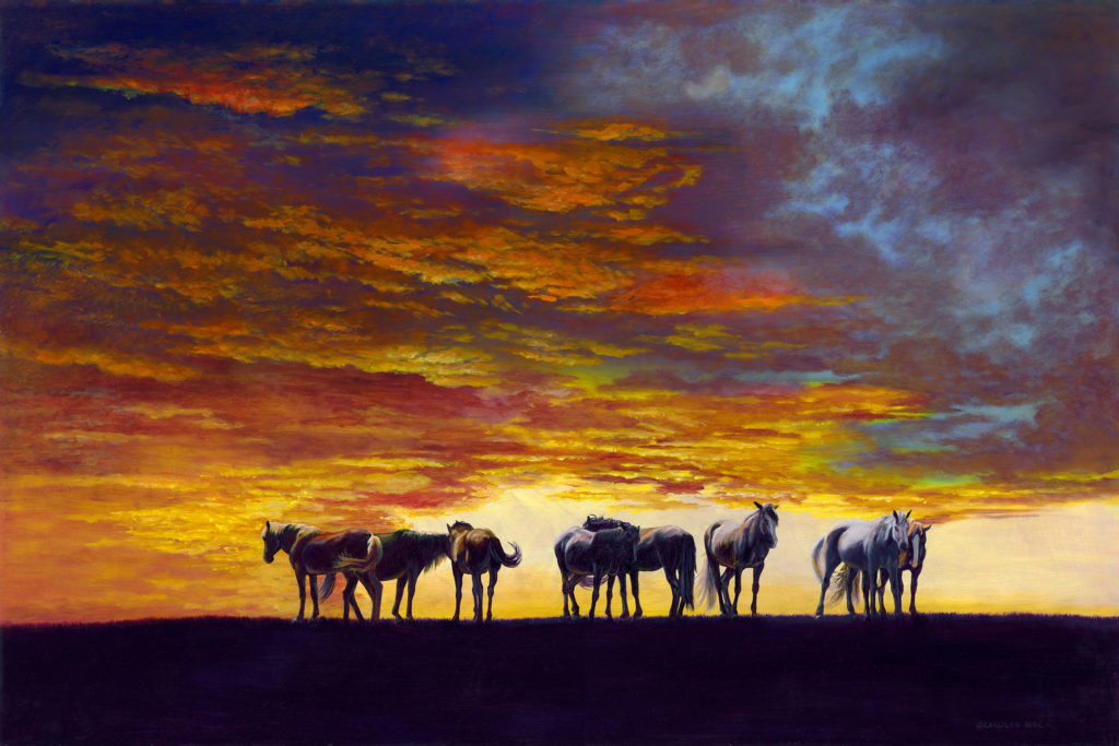 A herd of horses graze at sunset